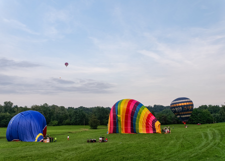 Biella, Italy, June 10, 2018 -Three hot air balloons being anchored and deflated after the flight, and one balloon in the sky at spring festival, June Pollone dal Cielo, Biella