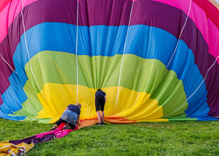 Biella, Italy, June 10, 2018 -Team of people work to pick up and fold the balloon towel after the flight at spring festival, June Pollone dal Cielo, Biella