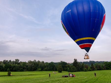 Biella, Italy, June 10, 2018 - Hot Air balloon in flight in phase of landing at the spring festival, June Pollone dal Cielo, Biella
