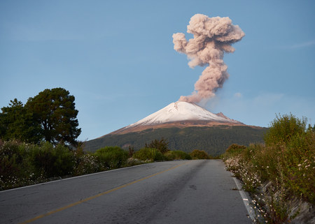 Column of smoke on Popocatepetl volcano seen from the street Ruta de Evacuación, puebla, Mexico