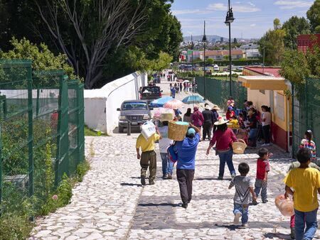 Mexican people and tourists walk along the street on archaeological area
