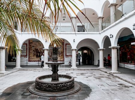 Colonnade with arches and fountain in square of San Pedro Cholula town hall.