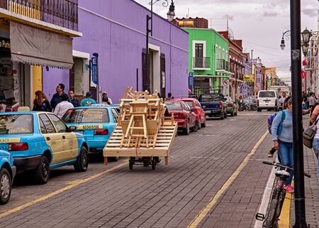 Craftsman transports furniture by hand in handcart on street of San Pedro Cholula. 新闻类图片