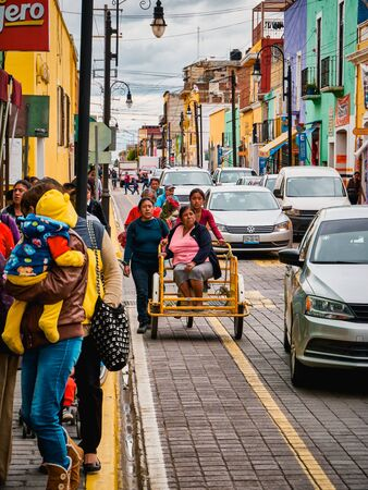 Mexican young women push a tricycle with an elderly woman