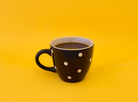 Black cup of coffee with white dot on yellow background