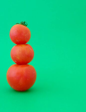 Three red tomatoes on cyan green background with copy space 免版税图像