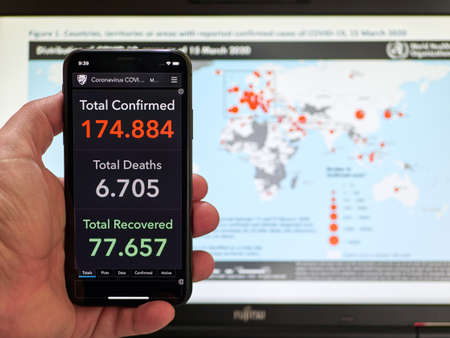 People holds smartphone with Coronavirus COVID-19 live statistic
