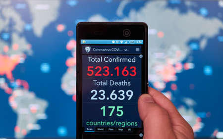 Smartphone with updated Coronavirus COVID-19 and world map of infected states in background 新闻类图片