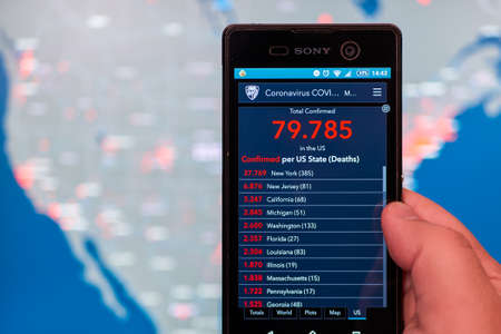 Man holds smartphone with updated Coronavirus COVID-19 live statistic of Confirmed Cases by US County and map of United States in background, Mexico, in March 26, 2020