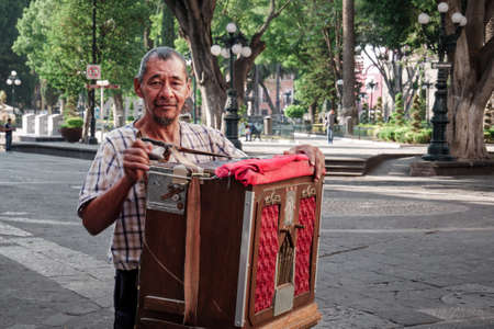 Street performer of Organillero or Cilindrero organ grinder plays the street organ in the Zocalo of Puebla City during the coronavirus outbreak, Mexico, in April 24, 2020 新闻类图片