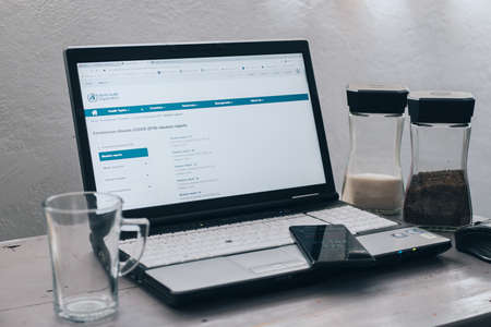 Laptop with website of World Health Organization at page of Coronavirus Disease (Covid-19) situation report, notebook on wooden table with jar of coffee and cup, Mexico, May 14, 2020 新闻类图片