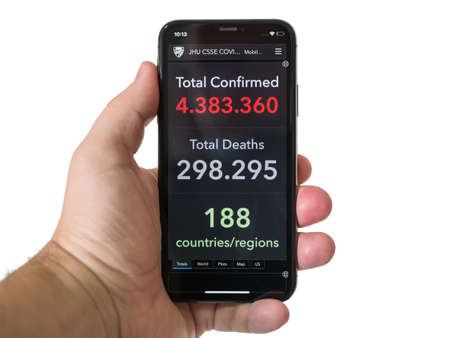 Man hand holds smartphone with COVID-19 Coronavirus website Confirmed Cases with over 4 million sick people for Systems Science and Engineering at Johns Hopkins University, Mexico, May 14, 2020