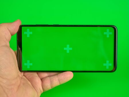 Mans hand holding a mobile phone with a horizontal green screen, chroma key smartphone technology 免版税图像
