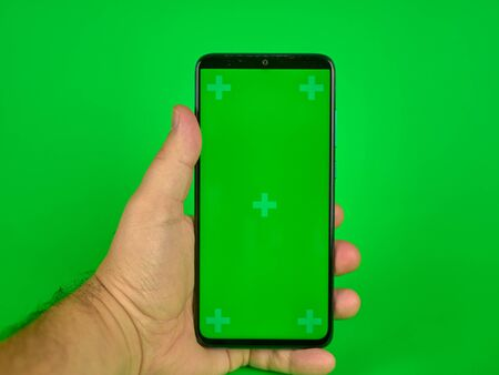 Mans hand holding a mobile phone with a vertical green screen, chroma key smartphone technology, view cellular screen
