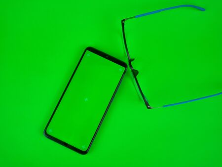 Mobile phone with a vertical green screen and glasses, chroma key smartphone technology 免版税图像