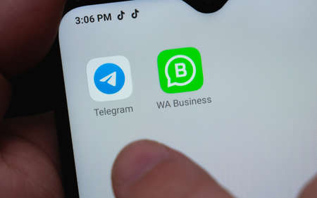 Crop anonymous person using smartphone with icons of Telegram and Whatsapp messenger apps for communication, Mexico, in February 8, 2021