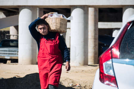 Young male local vendor without protective mask in red apron carrying wicker basket with goods on street of Mexico during   pandemic, Amecameca, in January 25, 2021 新闻类图片