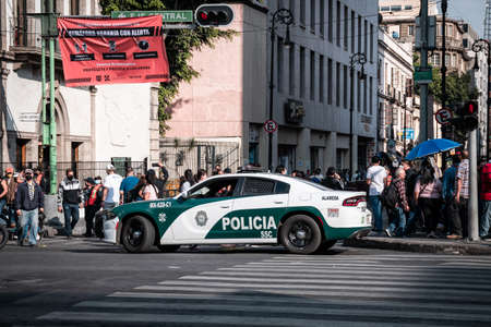 Modern police vehicle parked on road near crowd of people and blocking city during coronavirus epidemic in Mexico City, December 12, 2020 新闻类图片