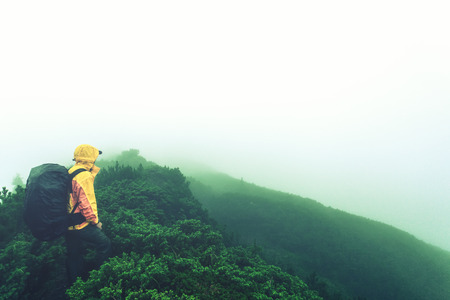 Tourist with backpack in the misty mountains photo