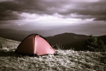 Red tent under clouds in mountains Zdjęcie Seryjne