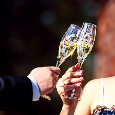 Celebratory glass of champagne in hand of bride