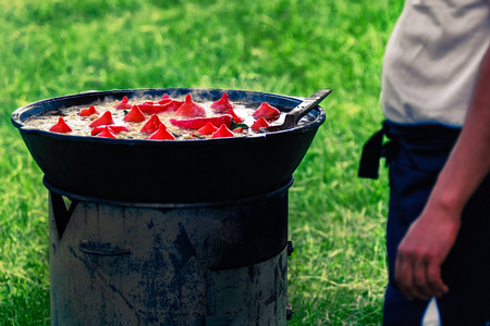 trivet: Cook prepares Uzbek Pilaf with paprika