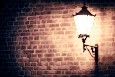 Lantern on brick wall of old city, blur