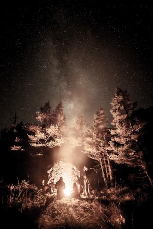 星空の下で火のそばの観光客