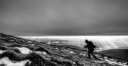 Climber fights with bad weather in the winter mountains.