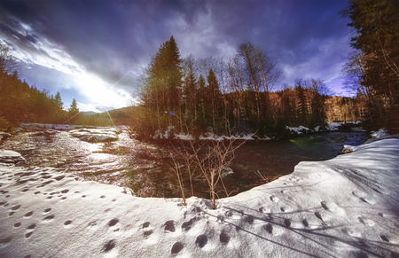 Mountain river covered with fresh snow, New Years holidays in Carpathians