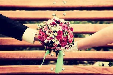 Newlyweds with wedding bouquet on a bench Zdjęcie Seryjne