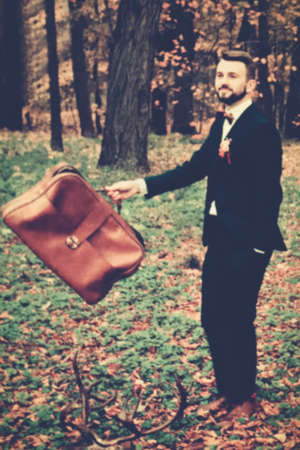 Vintage wedding in the old park, groom with a suitcase, blur