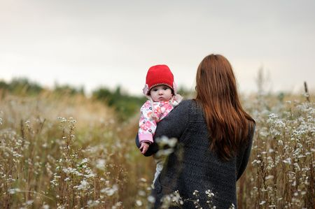 Mother holding her baby wearing red hat in arms Stock Photo - 5609957