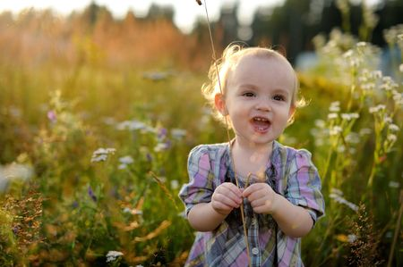 Little baby girl smiling in overgrown grass  Stock Photo - 5520809