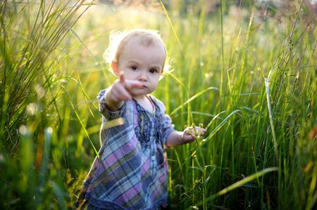 Little baby girl in overgrown grass pointing with her finger at you Stock Photo - 5520808