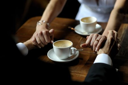 Bride and groom holding each others hands while sitting at the table photo