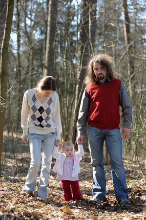 Young couple with their baby walking in the forest Stock Photo - 5609959