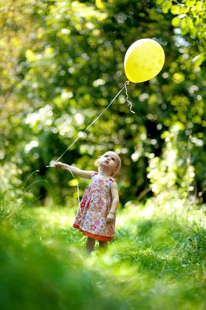 Little baby girl with a yellow balloon in the forest