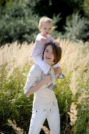 Mother giving piggyback ride to her baby pointing at you wih a finger Stock Photo - 5533234