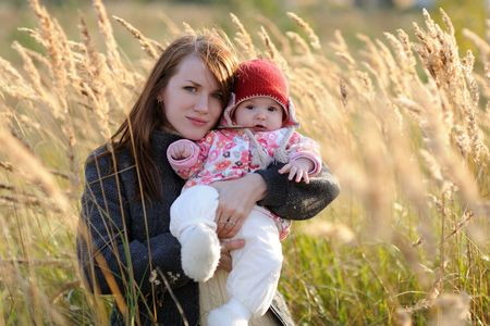 Young mother holding her little baby in a meadow Stock Photo - 5533218