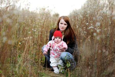 Young mother with her little baby in an overgrown grass Stock Photo - 5533308