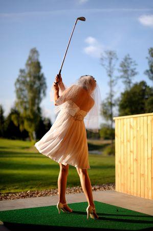Bride in wedding dress is playing golf