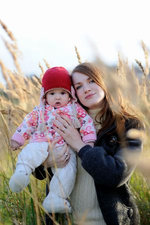 Young mother is holding her little baby walking in a meadow Stock Photo - 5609910