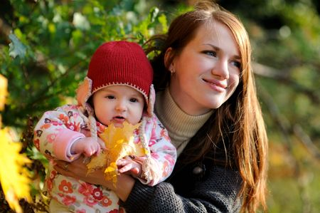 Young mother is holding her little baby and smiling Stock Photo - 5609911