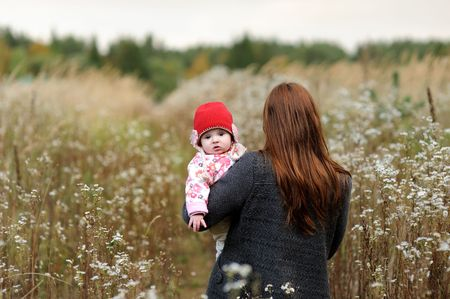 Mother is carryng her little baby girl accross the meadow Stock Photo - 5609954