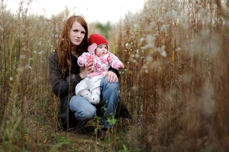 Young mother and her little baby in a meadow Stock Photo - 5609956