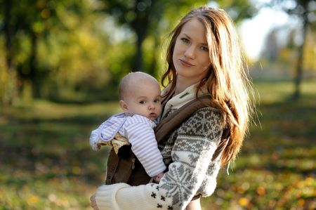 Young mother with her little baby in a carrier photo