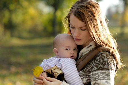 Young mother with her little baby in a carrier Stock Photo - 5609953