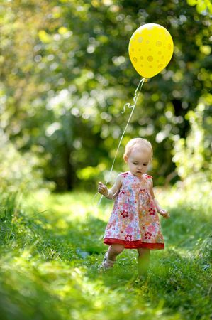 Little baby girl with a yellow balloon in a forest