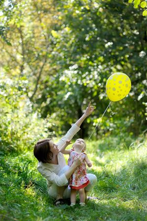 Young mother and her little baby looking at the yellow balloon photo